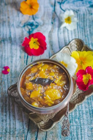 raw mango pachidi served in a copper bowl and a tray full of flowers.