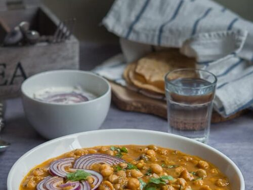 Channa masala or chole masala displayed in a white bowl with raita, roti and a glass of water.