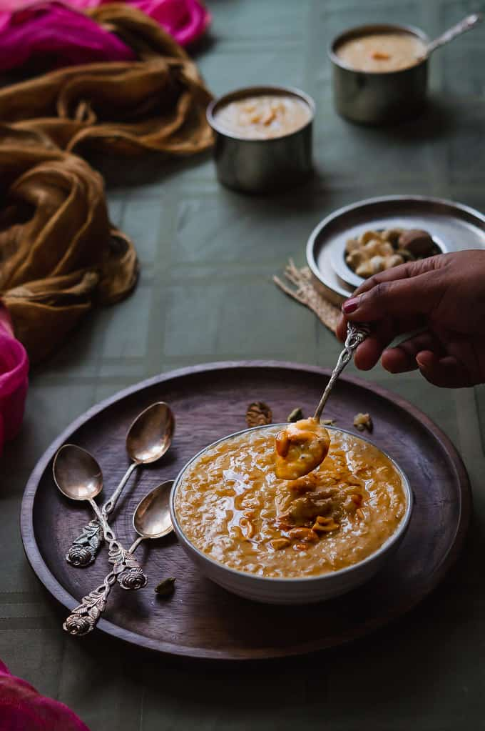 Traditional Akkaravadisal recipe in a white ceramic bowl that is scooped.