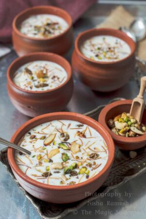 semiya payasam vermiceli kheer in a clay bowl and exotic nuts on the side.