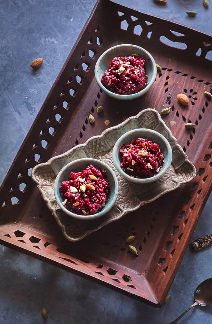 beetroot halwa shot on a top down angle displayed on a tray in three green ceramic bowls.