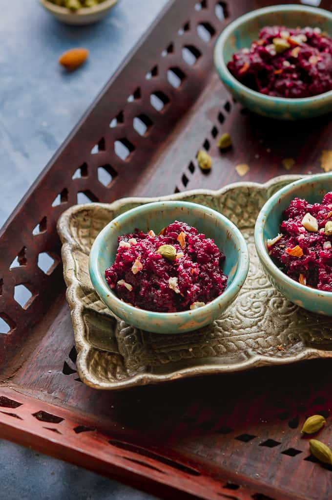 Beetroot halwa displayed on small green bowls and served in a wooden tray.