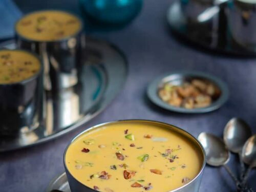 Carrot payasam displayed in stainless steel bowl with lots of nuts and raisins