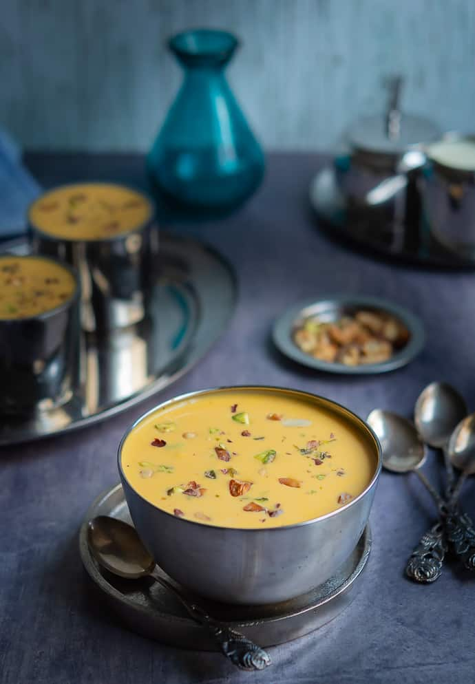 carrot payasam displayed on a stainless steel bowl with lots of nuts garnished.