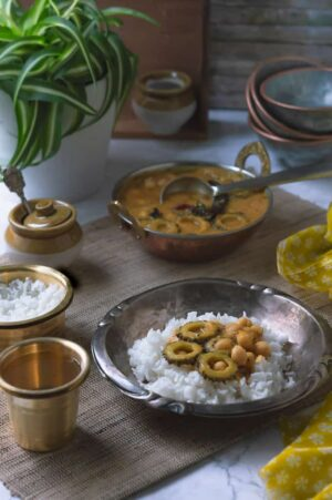 Paavakai Pitla displayed with a hand model pouring on a plate with white steamed rice.
