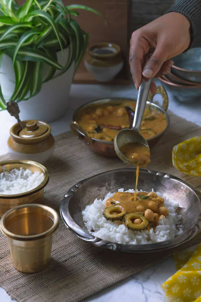 Paavakai Pitla displayed with a hand model pouring on a plate with white steamed rice