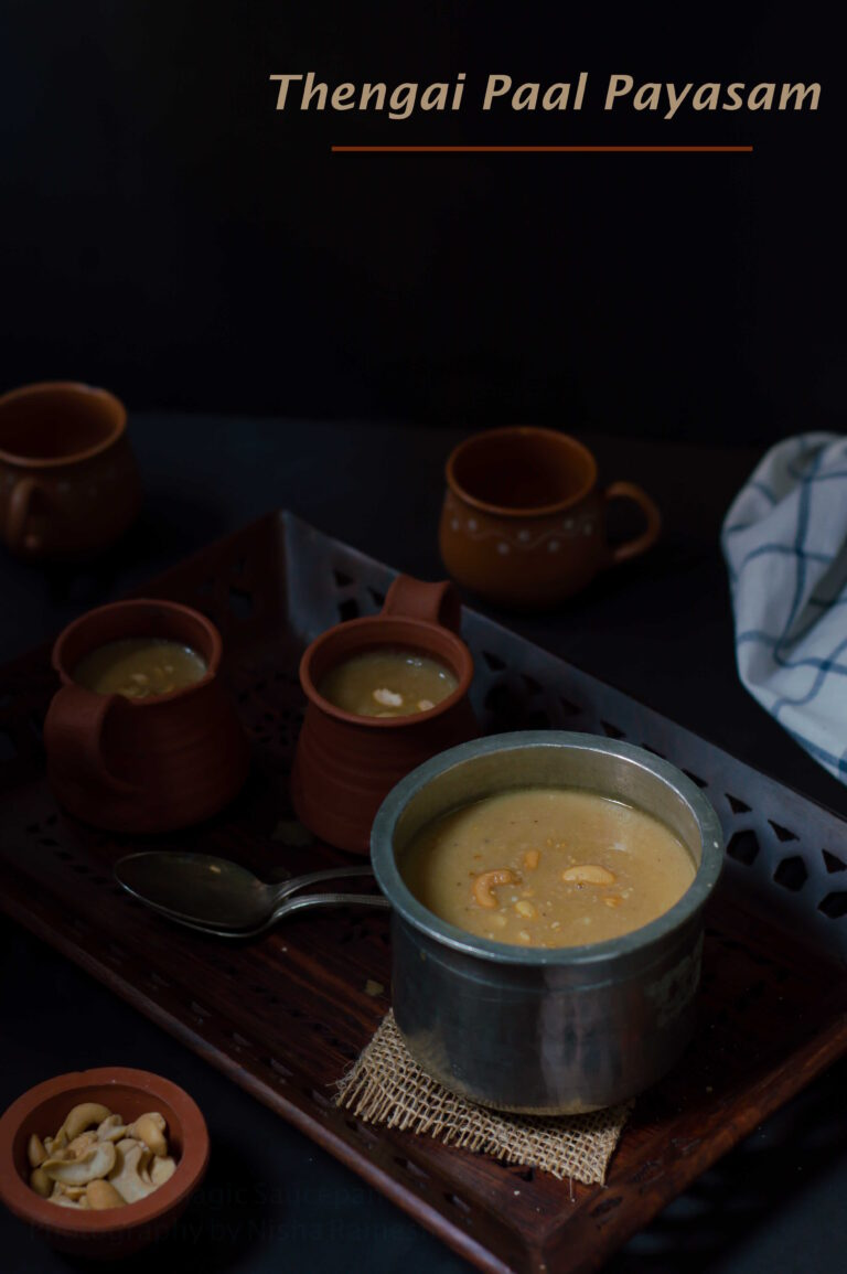 Thengai Paal Payasam displayed in tall vessel in a dark moody background.