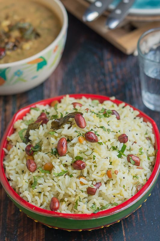 A close up shot of Mangai Sadam or Raw Mango rice in a red and green colourful bowl topped with roasted peanuts.