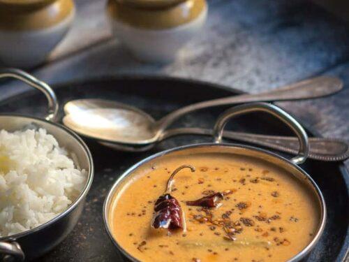 thengai aracha kuzhambu displayed on a small indian kadai with small indian jars and a bowl of rice.