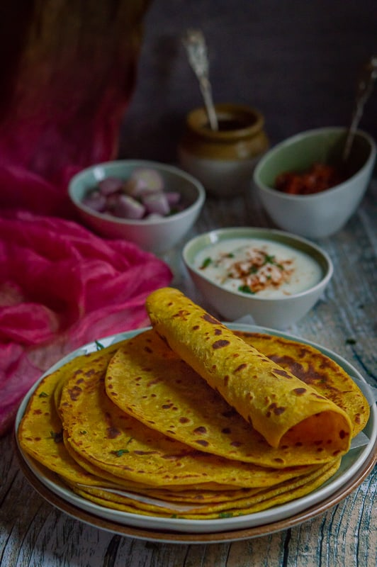 Besan masala roti or gram flour roti is stacked on a plate with the top one rolled in half.