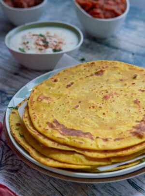 Besan masala roti or gram flour roti is stacked on a plate with yogurt and tomato curry on the side.