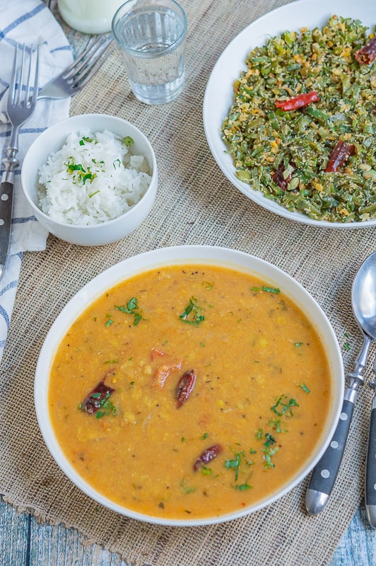A top down shot of Arachuvitta sambar displayed on a white shallow bowl with broad beans curry and a bowl of rice.