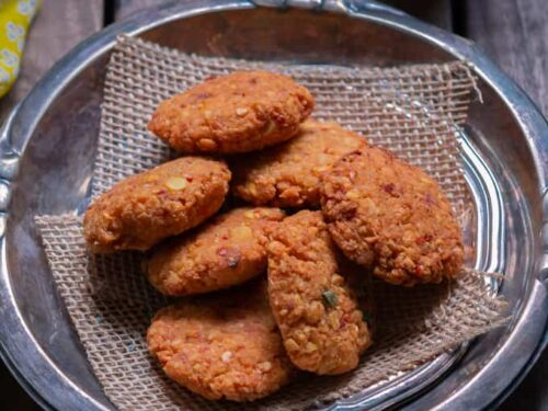 Stack of vada on a brass plate and with a glass of water.